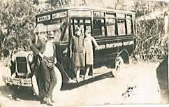 Visitors on the step of a tourist bus in the early 1920s